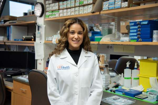 Female research with white lab coat smiling inside lab