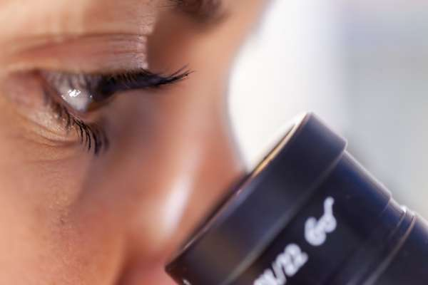 a close-up shot of a woman peering into a microscope
