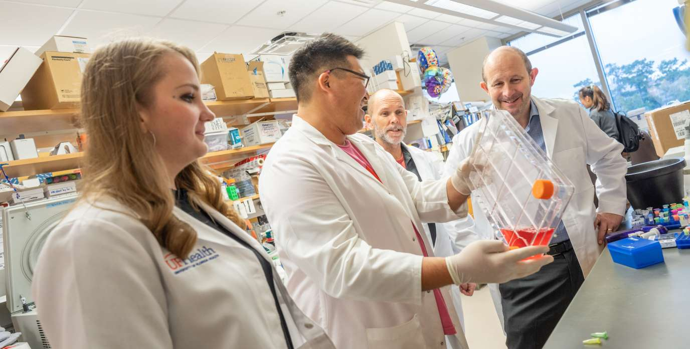 doctors Todd Golde and Cara Croft collaborate with trainees in the lab.